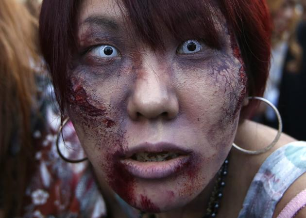 "A participant dressed as a zombie marches during a Halloween event to promote the U.S. TV series ""The Walking Dead"" at Tokyo Tower"