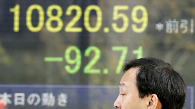 A man walks by an electronic stock board of a securities firm in Tokyo, Monday, Jan. 21, 2013. Asian stock markets were mixed Monday amid uncertainty about the outcome of a central bank meeting in Japan and nervousness over whether U.S. political leaders will be able to reach a deal on the government's debt limit. (AP Photo/Koji Sasahara)