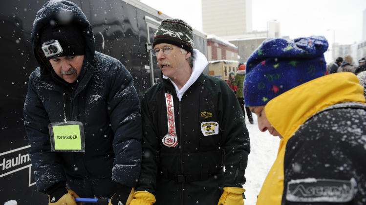 Jeff King, center, talks with his Iditarider, left, before the ceremonial start of the Iditarod trail sled dog race, Saturday, March 3, 2012, in Anchorage, Alaska. (AP Photo/The Anchorage Daily News, Marc Lester)