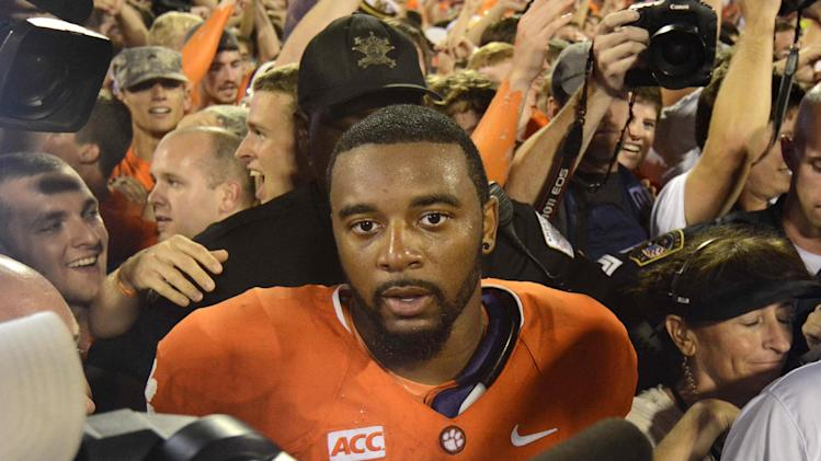 Clemson quarterback Tajh Boyd is surrounded by fans and newspeople after defeating Georgia 38-35 in an NCAA college football game Saturday, Aug. 31, 2013 at Memorial Stadium in Clemson, S.C.(AP Photo/ Richard Shiro)