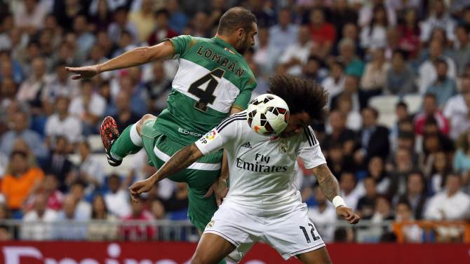 Real Madrid's Marcelo and Elche's Lomban challenge for the ball during their Spanish first division soccer match in Madrid
