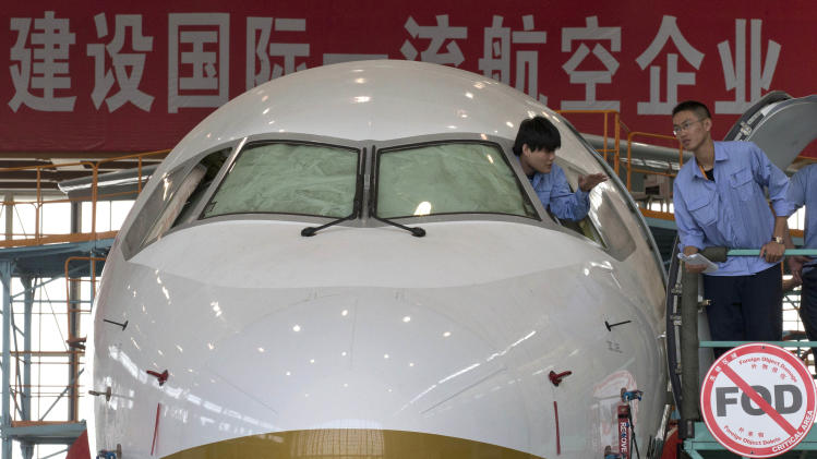 A worker peers out from the cockpit of an almost completed COMAC ARJ21-700 passenger jet at a final assembly and manufacturing center in Shanghai , China, Wednesday, May 21, 2014. China's state-owned plane maker Comac said Wednesday they were ready to deliver their first regional airliner and were on track to deliver their greater distance-flying narrow-body airplane to customers in 2018. (AP Photo/Ng Han Guan, Pool)