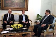 Egyptian President Mohamed Morsi (R) and Foreign Minister Mohammed Kamel Amr (L) meet with German Foreign Minister Guido Westerwelle (C) at the Presidential Palace in Cairo
