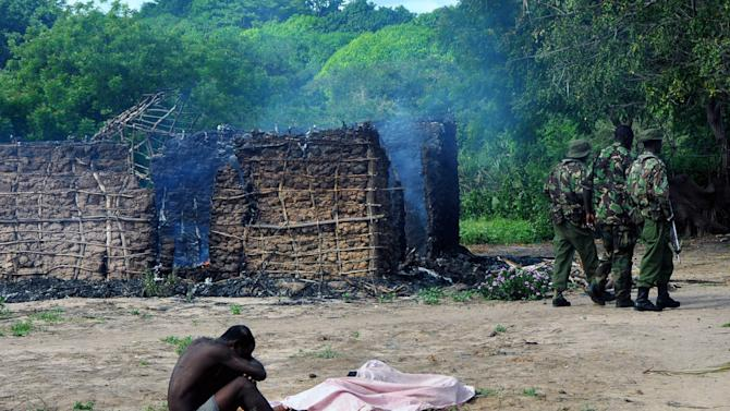 Security officers walk away as a man mourns next to the bodies of his wife and a daughter who were gunned down outside their house as they attempted to escape when suspected Orma raiders attacked their Kibusu as suspected Orma raiders attacked their village Kibusu  in Kenya Thursday Jan. 10, 2013. The raiders set more than twenty houses on fire and killed at least ten people as the Tana River County ethnic clashes erupted yet again.  (AP Photo)