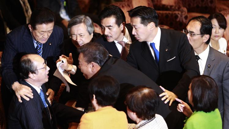 Nakagawa, chairman of the Upper House Special Committee on National Security, is surrounded by lawmakers during a vote on a state secrets act at the parliament in Tokyo