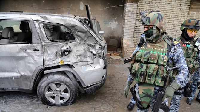 Security forces inspect the site of a car bomb attack in Baghdad's Karrada neighborhood, Iraq, Wednesday, Nov. 20, 2013. A wave of attacks, mostly by car bombs, hit mainly Shiite and commercial areas of Baghdad on Wednesday morning, killing and wounding civilians officials said. (AP Photo/ Karim Kadim)