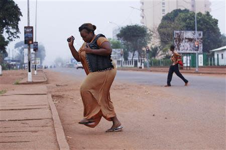 A woman runs from gunfire in Bangui