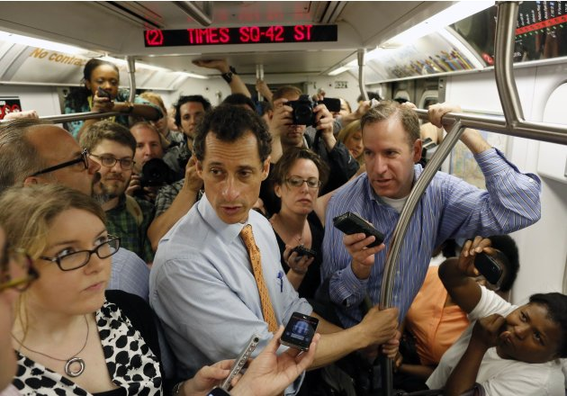 Former U.S. Congressman and New York City mayoral candidate Anthony Weiner talks with reporters while riding the subway between campaign events in New York