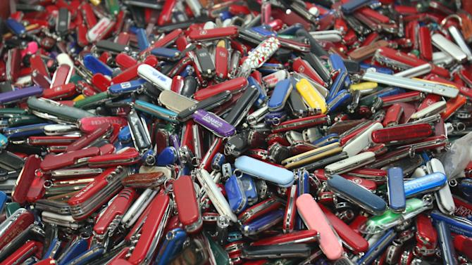 FILE - In this Sept. 26, 2006, file photo, knives of all sizes and types are piled in a box at the State of Georgia Surplus Property Division store in Tucker, Ga., and are just a few of the hundreds of items discarded at the security checkpoints of Hartsfield-Jackson Atlanta International Airport that will be for sale at the store. Airline passengers will be able to carry small knives, souvenir baseball bats, golf clubs and other sports equipment onto planes beginning in April 2013 under a policy change announced Tuesday, March 5, 2013, by the head of the Transportation Security Administration administrator John Pistole. (AP Photo/Gene Blythe, File)