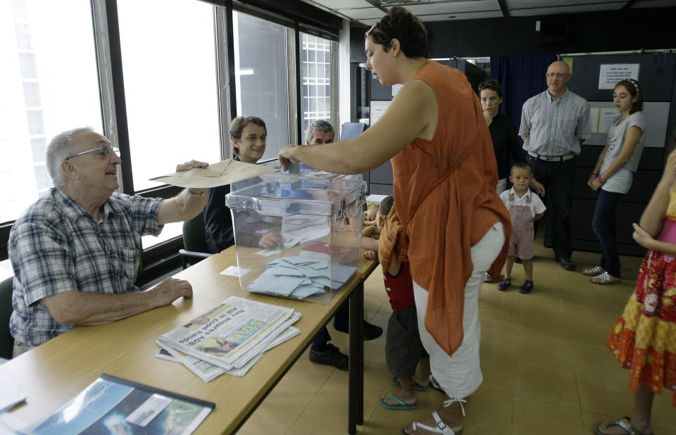 French citizens cast their vote in their country's presidential election at an overseas voting center inside the French Embassy in Makati, south of Manila, Philippines on Sunday, May 6, 2012. French citizens are choosing between Conservative President Nicolas Sarkozy and Socialist challenger Francois Hollande as they vote during the final round of presidential elections Sunday.(AP Photo/Aaron Favila)