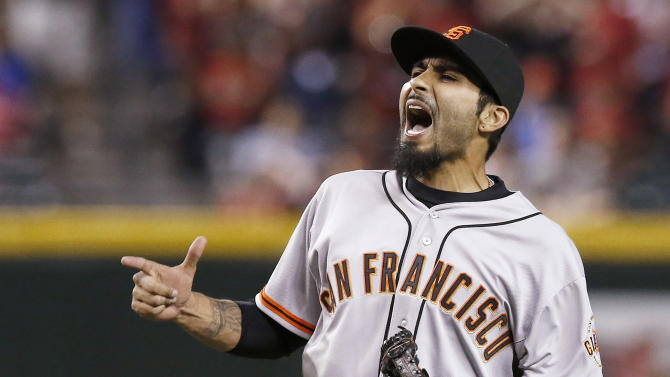 In a March 31, 2014, file photo San Francisco Giants' Sergio Romo celebrates the final out against the Arizona Diamondbacks during the ninth inning of an opening day baseball game  in Phoenix.  A person with knowledge of the negotiations says free agent reliever Sergio Romo is closing in on a new contract with the San Francisco Giants