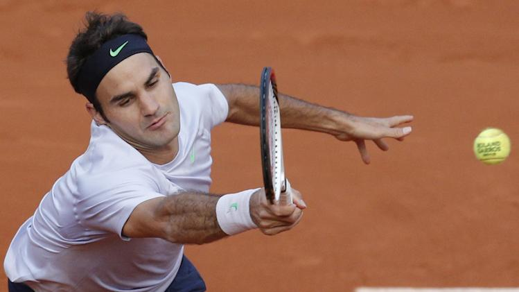 Switzerland's Roger Federer returns against France's Gilles Simon, defeating Simon in five sets 6-1, 4-6, 2-6, 6-2, 6-3, in their fourth round match at the French Open tennis tournament, at Roland Garros stadium in Paris, Sunday June 2, 2013. (AP Photo/Christophe Ena)