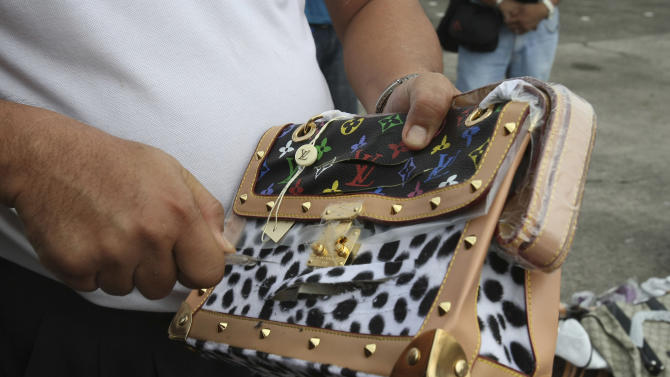 A Government worker uses a cutter to slash a counterfeit Louis Vuitton handbag during a ceremonial destruction of counterfeit goods seized in raids recently at parade grounds of the Philippine National Police at suburban Quezon city, northeast of Manila, Thursday June 30, 2011. The ceremonial destruction of pirated DVDs and other counterfeit goods was done to coincide with the global celebration and awareness campaign known as World Anti-Counterfeiting Day. (AP Photo/Bullit Marquez)