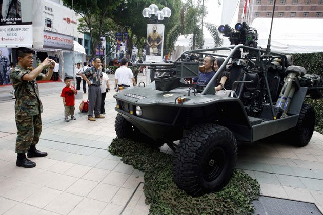 A Singapore military personnel takes photograph of a couple sitting in a light strike vehicle displayed along Orchard Road walkway which is part part of a show to commemorate 40 years of National Service in Singapore, 12 April 2007. (AFP photo)