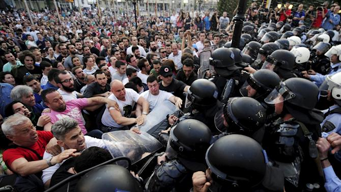 Protestors fight with police in front of a Macedonian government building in Skopje