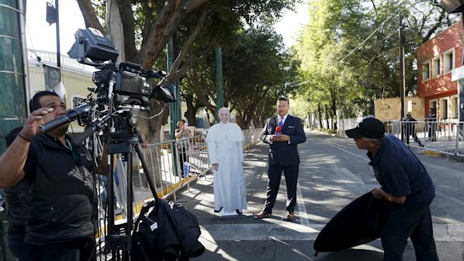 A TV journalist does a dispatch next to a cardboard cut-out of Pope Francis in Mexico City