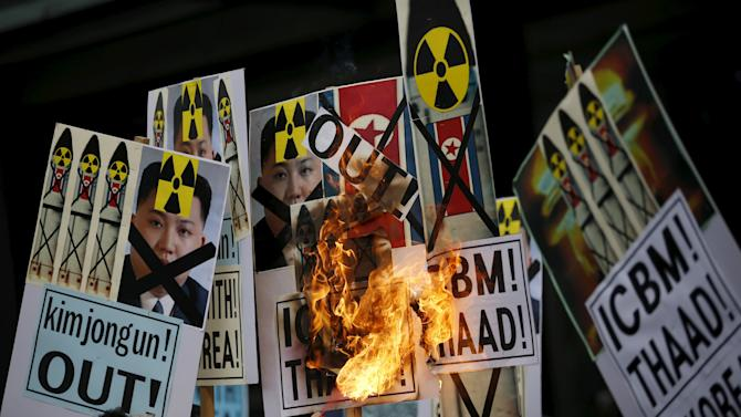 A man burns banners being held by protesters during an anti-North Korea rally in central Seoul