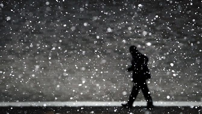 A traveler at the Memphis Airport hustles through the flakes of falling snow to make his flight Monday, March 3, 2014 after a winter storm covered parts of Memphis in a blanket of ice over night. (AP Photo/The Commercial Appeal, Jim Weber)