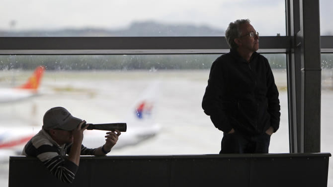 A man uses a telescope to look at planes at Kuala Lumpur International Airport in Sepang, Malaysia, Tuesday, March 18, 2014. Checks into the background of all the Chinese nationals on board the missing Malaysian jetliner have uncovered no links to terrorism, the Chinese ambassador in Kuala Lumpur said Tuesday. (AP Photo/Lai Seng Sin)