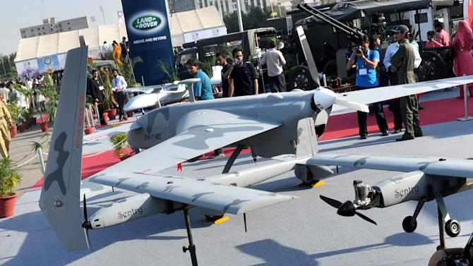 In this Thursday, Nov. 15, 2012 photo, visitors look at Pakistan-made unmanned aircraft at defense exhibition in Karachi, Pakistan. Pakistan is secretly racing to develop its own armed drones, frustrated with U.S. refusals to provide the aircraft, but is struggling in its initial tests with a lack of precision munitions and advanced targeting technology. The development of unmanned combat aircraft is especially sensitive in Pakistan because of the widespread unpopularity of U.S. drone strikes against militants in the rugged tribal region bordering Afghanistan.(AP Photo/Shakil Adil)