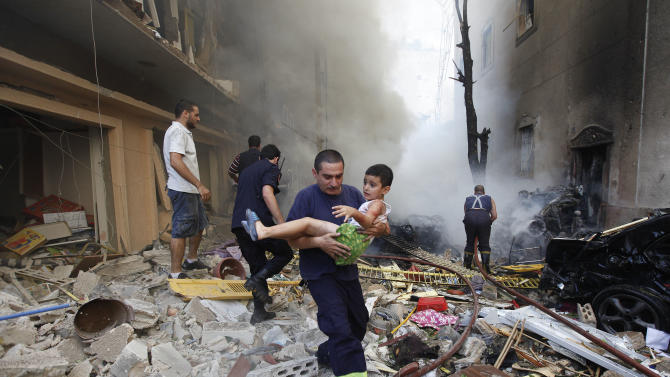A Lebanese rescue man, carries an injured boy at the scene of an explosion in the mostly Christian neighborhood of Achrafiyeh, Beirut, Lebanon, Friday Oct. 19, 2012. A car bomb ripped through eastern Beirut on Friday, shearing the balconies off residential buildings and sending bloodied victims pouring out into the streets in the most serious blast this city has seen in years. (AP Photo/Hussein Malla)