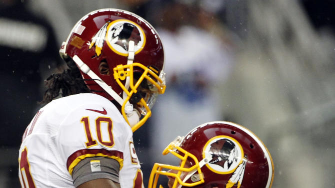 Washington Redskins quarterback Robert Griffin III (10) and Kory Lichtensteiger (78) celebrate a touchdown in the first half of an NFL football game against the Dallas Cowboys, Thursday, Nov. 22, 2012, in Arlington, Texas. (AP Photo/Tim Sharp)