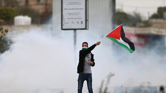 Protester waves a Palestinian flag in front of tear gas fired by Israeli troops during clashes at Hawara checkpoint near Nablus