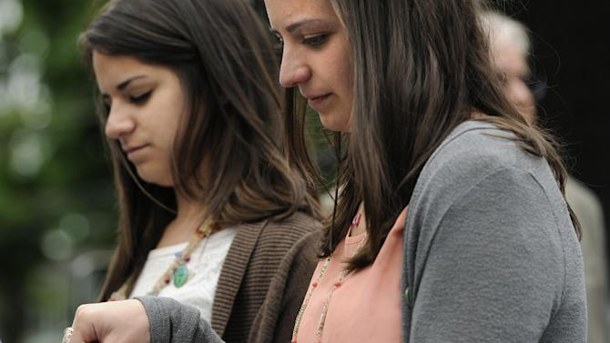 Carlee Soto, left, and Jillian Soto, sisters of slain teacher Victoria Soto, hold hands during a 26-second moment of silence at Edmond Town Hall honoring the 20 children and six adults gunned down at Sandy Hook Elementary School on Dec. 14, 2012 in Newtown, Conn., Friday, June 14, 2013. Newtown held a moment of silence Friday for the victims of the massacre at Sandy Hook Elementary School at a remembrance event that doubled as a call to action on gun control, with the reading of names of thousands of victims of gun violence. (AP Photo/Jessica Hill)