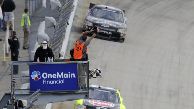 Joey Logano (18) takes the checkered flag to win the NASCAR Nationwide Series auto race, Saturday, Sept. 29, 2012, at Dover International Speedway in Dover, Del. Paul Menard finished in second place. (AP Photo/Nick Wass)