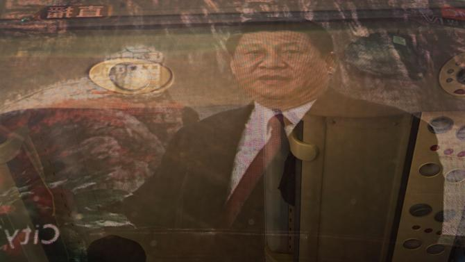 A bus driver smokes inside a bus as a screen showing a live broadcast of China's new Communist Party General Secretary Xi Jinping speaking during a press event to introduce the newly-elected members of the Politburo Standing Committee, is reflected in the window, in Beijing Thursday, Nov. 15, 2012. The seven-member Standing Committee, the inner circle of Chinese political power, was paraded in front of assembled media on the first day following the end of the 18th Communist Party Congress. (AP Photo/Andy Wong)
