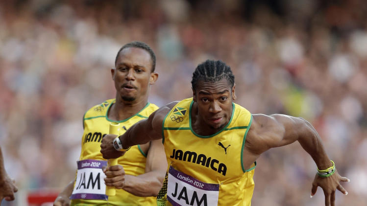 Jamaica's Michael Frater, left, passes the baton to Yohan Blake in a men's 4x100-meter relay heat during the athletics in the Olympic Stadium at the 2012 Summer Olympics, London, Friday, Aug. 10, 2012. (AP Photo/Hassan Ammar)