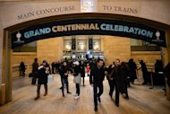 People walk under a banner set up as part of the centennial celebrations for Grand Central Terminal in New York, February 1 , 2013. Grand Central Terminal, the doyenne of US train stations, is celebrating its 100th birthday on February 2, 2013