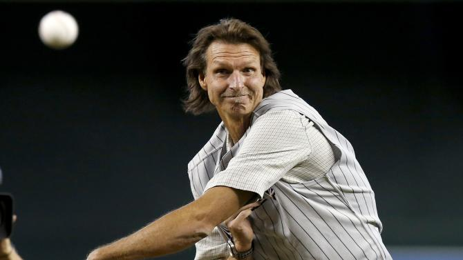 Former Arizona Diamondbacks pitcher Randy Johnson throws out the first pitch during ceremonies commemorating the 10th anniversary of Johnson's perfect game prior to a baseball game between the Diamondbacks and the Los Angeles Dodgers on Sunday, May 18, 2014, in Phoenix