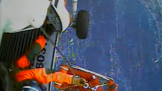 In this image made from video and released by the U.S. Coast Guard, a USCG crew member uses a hoist to bring up a survivor into a helicopter. A replica tall ship caught in Hurricane Sandy's wrath began taking on water, forcing the crew to abandon the boat Monday in rough seas off the North Carolina coast. The Coast Guard rescued 14 crew members by helicopter, but two people were still missing. (AP Photo/U.S. Coast Guard)