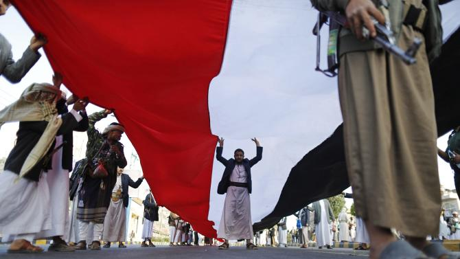 Houthi followers carry a large Yemeni flag during a demonstration to show support to the movement in Sanaa