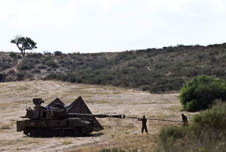 Israeli soldiers clean the barrel of a mobile artillery unit outside central Gaza