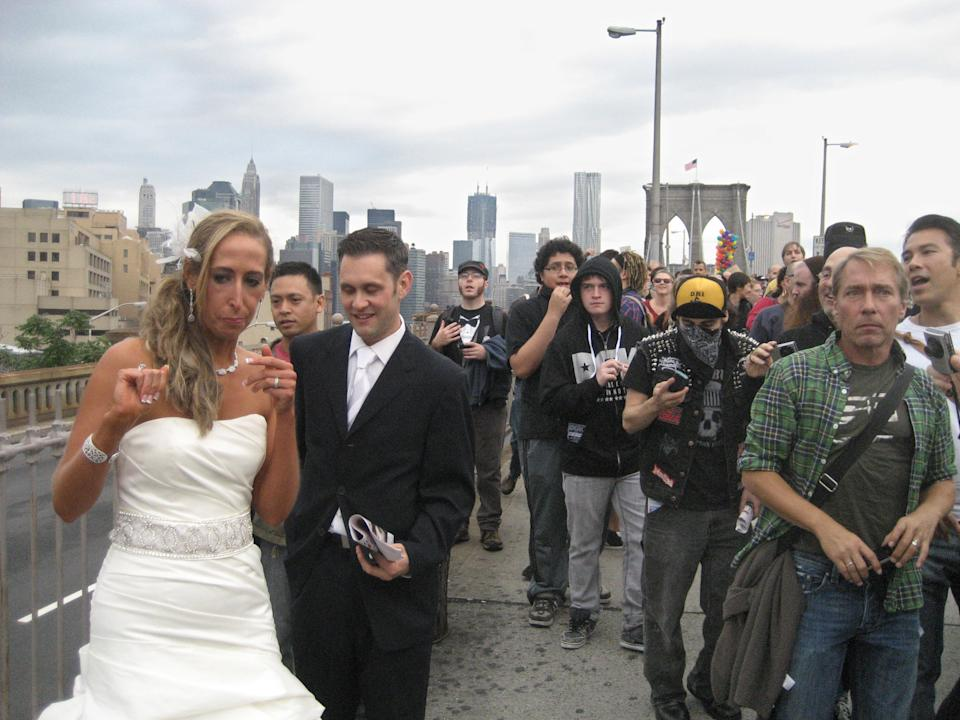 Occupy Wall Street movement protesters take photos of a couple while marching across the Brooklyn Bridge in New York, Saturday, Oct. 1, 2011. Police arrested hundreds of protesters Saturday. (AP Photo/Daryl)