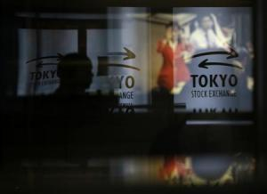 A visitor walks past logos at the TSE in Tokyo