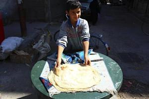A boy makes bread in Duma neighbourhood, in Damascus