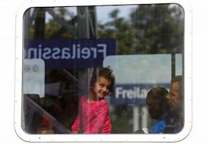 A child smiles as migrants sit on a train at a station …