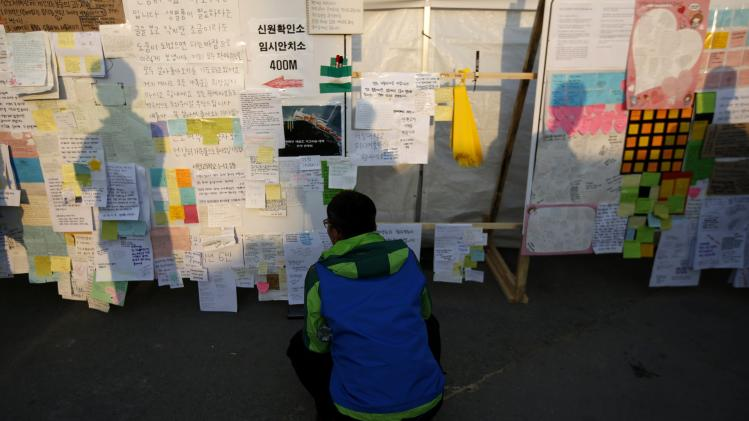 A family member of missing passengers onboard the sunken South Korean ferry Sewol, looks at messages at a port in Jindo