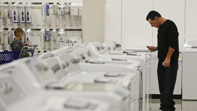 In this Friday, Nov. 23, 2012, photo, a man examines a row of washers and dryers while shopping at a Sears store in Henderson, Nev. U.S. companies increased their orders for long-lasting manufactured goods in November, with a second consecutive monthly gain in a key category that reflects businesses' investment plans.  The Commerce Department reported Friday, Dec. 21, 2012, that orders for durable goods rose a seasonally adjusted 0.7 percent in November, compared to October, when orders had risen 1.1 percent. (AP Photo/Julie Jacobson)