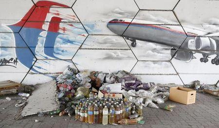 A man sleeps under graffiti depicting flight MH370 on the one year anniversary of its disappearance in Kuala Lumpur