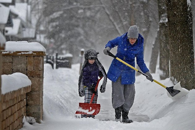 Amy Wolf and her daughter Audrey Wolf, 6,  shovel the sidewalk on Friday, Feb.  22, 2013 in Minneapolis.   A major snowstorm that buried parts of the Midwest grazed southern Minnesota, where two to th
