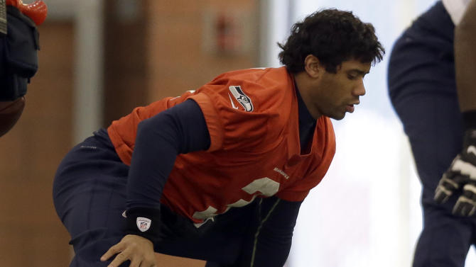 Seattle Seahawks quarterback Russell Wilson stretches at the start of NFL football practice Thursday, Jan. 30, 2014, in East Rutherford, N.J. The Seahawks and the Denver Broncos are scheduled to play in the Super Bowl XLVIII football game Sunday, Feb. 2, 2014. (AP Photo)