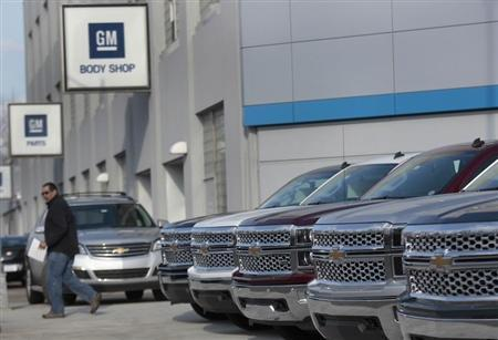 A man walks past a row of General Motors vehicles at a Chevrolet dealership on Woodward Avenue in Detroit, Michigan