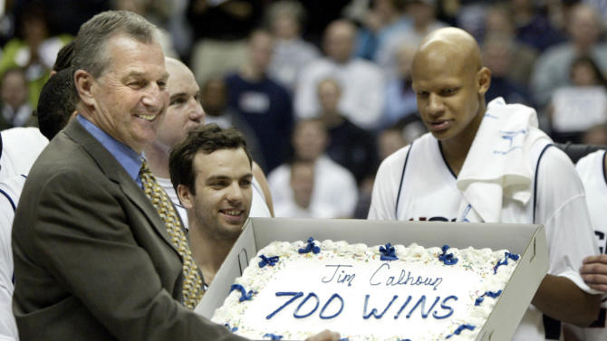 University of Connecticut head coach holds up a cake celebrating his 700th win.