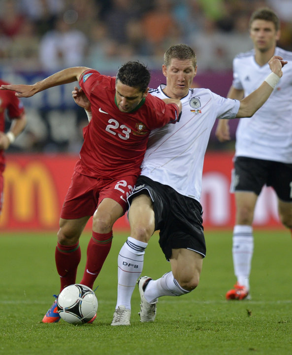 Portugal's Helder Postiga, left, and Germany's Bastian Schweinsteiger fight for the ball during the Euro 2012 soccer championship Group B match between Germany and Portugal in Lviv, Ukraine, Saturday,