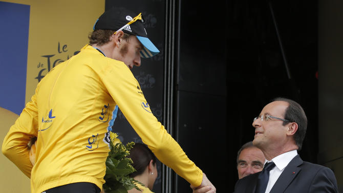Bradley Wiggins of Britain, wearing the overall leader's yellow jersey, is greeted by French President Francois Hollande on the podium of the 18th stage of the Tour de France cycling race over 222.5 kilometers (138.3 miles) with start in Blagnac and finish in Brive-la-Gaillarde, France, Friday July 20, 2012. (AP Photo/Christophe Ena)