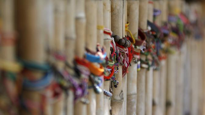 Multi-colored bracelets commemorating Khmer Rouge victims are tied on poles at a former mass graves site at Choeung Ek